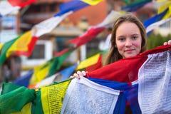 Teengirl und buddhistische Gebetsflaggen nepal Stockfotografie