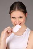 Teenlady en el resbalón bitting del papel Cierre para arriba Fondo gris Imagen de archivo libre de regalías