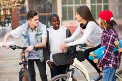Teens που κουβεντιάζει κοντά στα ποδήλατα Στοκ Εικόνες