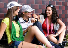 Teens 1. Students are sitting beside a wall and making a rest Royalty Free Stock Image