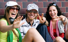 Teens 2. Students are sitting beside a wall and making a rest Royalty Free Stock Photo