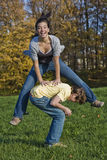 Teens. Caucasian teens one male and one female horsing around in a park playing leapfrog Stock Images