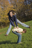 Teens. Caucasian teens one male and one female horsing around in a park playing leapfrog Stock Photos