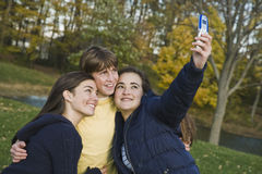 Teens. Three caucasian teens one male and two females horsing around in a park using a cell phone to take their pictures Royalty Free Stock Image