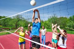 Teens all are with arms up play volleyball Royalty Free Stock Photography