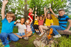 Teens with arms up near bonfire hold marshmallow Royalty Free Stock Photos