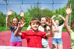 Teens with arms up play volleyball near the net Royalty Free Stock Photos