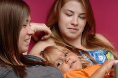 Teens baby-sit little girl Stock Photo
