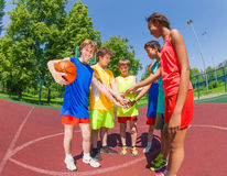 Teens before basketball hold arms in star shape Royalty Free Stock Images