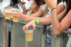Teens with beer. Hands of young girls with beer at a concert/event stock photos
