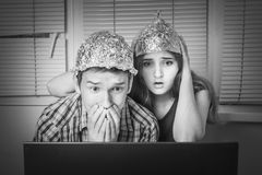 Teens boy and girl  in hats made of aluminum foil, protect the b. Teens boy and girl in hats made of aluminum foil looking frightened at laptop Royalty Free Stock Photo