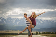 Teens boy and a girl on the road near the mountains Stock Photos