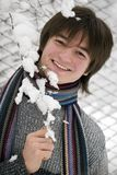 Teens boy with snown branch. Pretty  European teens boy with snown branch are laughing outdoors in winter Stock Photo
