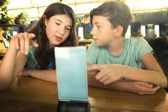Teens in cafee choosing menu for breakfast. Siblings brother and sister teens in cafee choosing menu for breakfast Stock Photo