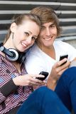 Teens with cellphones. Young couple sitting on ground, leaning back against wall Stock Photography
