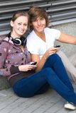 Teens with cellphones. Happy Teenagers Sitting by a Wall Royalty Free Stock Images