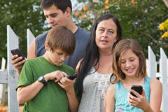 Teens on Cellphones. Exasperated mother with three teens distracted by their smartphones Stock Photography
