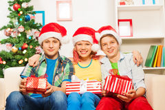 Teens with Christmas presents in home interior Stock Photo