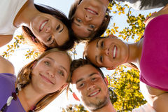 Teens in a circle smiling in park. Leisure students friends Royalty Free Stock Photography