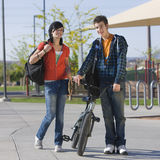 Teens couple walks together. Two teen kids walk through a park Stock Images