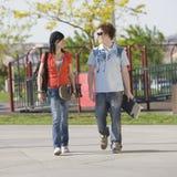 Teens couple walks together. Two teen kids walk through a park Stock Photo