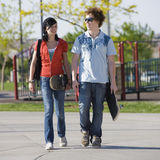 Teens couple walks together. Two teen kids walk through a park Stock Image