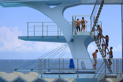 Teens on diving board. Boys and girls on diving tower of outdoor seaside swimming pool preparing to dive and looking to the sailing boats race in the sea Royalty Free Stock Image