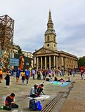 Teens painting at Trafalgar Square London England. Teens drawing at the pavement and costumed men statues levitating off the ground in front of the St Martin-in Royalty Free Stock Photos