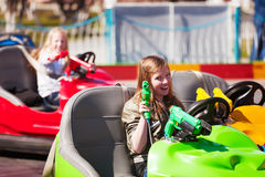 Happy teen girl driving bumper car Royalty Free Stock Photos