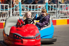 Young girls driving a bumper cars Stock Images