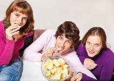 Teens eating crisps. Three cheerful teens eating crisps royalty free stock photography