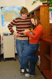 Teens flirting in Library. A boy flirts with a teen girl in the library Stock Images