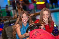 Teens at fun fair riding dodgems. Or bumper cars Stock Photo