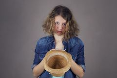 Teens girl with a sad face asks for money. Teens girl with a sad face holds an empty straw hat and asks for money royalty free stock photography