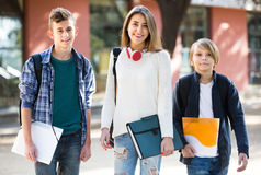 Teens going to school with papers Stock Image