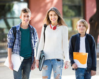 Teens going to school with papers Royalty Free Stock Photo