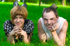Teens on grass. Teenagers: girl and fellow are lying on green grass. They see forward. Green grass around them Royalty Free Stock Photo