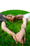 Teens on grass (fisheye). Teenagers: girl and fellow are lying on green grass. They see forward. Their hands together. Green grass around them Royalty Free Stock Photography