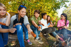 Teens grilling sausages sitting near yellow tent Royalty Free Stock Images