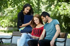 Teens hanging out outside and doing homework Stock Photography