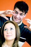 Teens Having Fun. A teenage boy holding his hands over a teen girls head royalty free stock images