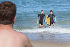 Teens having fun with bodyboard at beach Stock Photo