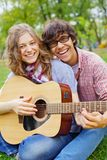 Teens having fun with guitar in park royalty free stock image