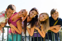 Teens having fun in park leaning fence Royalty Free Stock Photos
