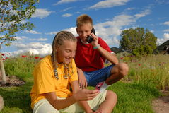 Teens having fun with phones. Children having fun with phones in a meadow with dramatic blue sky Royalty Free Stock Photo