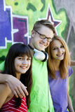 Teens with headphones near graffiti wall. Royalty Free Stock Image