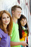 Teens with headphones near graffiti wall. Royalty Free Stock Photography
