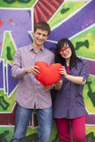 Teens with heart near graffiti wall. Royalty Free Stock Photos