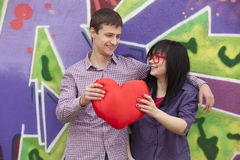 Teens with heart near graffiti wall. Royalty Free Stock Photo