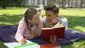 Teens hiding behind book and kissing, lying on plaid in park, first relations stock footage